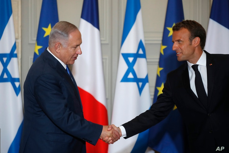 French President Emmanuel Macron and Israel's Prime Minister Benjamin Netanyahu shake hands as they attend a joint press conference at the Elysee Palace in Paris, June 5, 2018.
