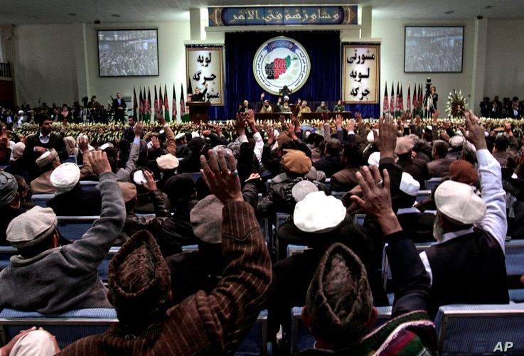 Members of the Afghan national consultative council known as the Loya Jirga attend the last day of the assembly in Kabul, Afghanistan, Sunday, Nov. 24, 2013
