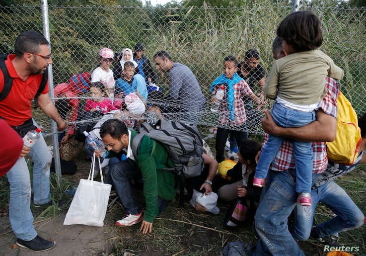 Migrants pass under highway security fence as they try to find a new way to enter Hungary after Hungarian police sealed the border with Serbia near the village of Horgos, Serbia, Sept. 14, 2015, near the Hungarian migrant collection point in Roszke. ...
