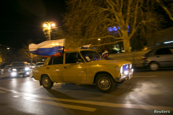 Motorist displays Russian flags ahead of referendum widely expected to transfer control of Black Sea peninsula from Ukraine to Moscow, Sevastopol, March 15, 2014.