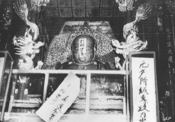 """FILE - In this file photo taken Aug. 27, 1966, a Buddha statue is covered with signs reading """"Destroy the old world,"""" and """"Establish a new world,"""" by ultra-patriotic Red Guard who reject ancient Chinese traditions at Lin Yin temple in Hangzhou, easte..."""