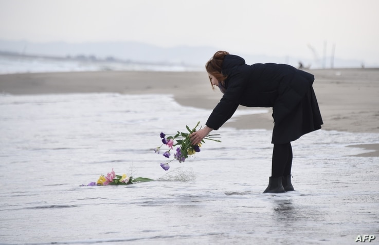 A woman puts flowers into the sea to pray for victims of the 2011 earthquake and tsunami in Sendai, northern Japan, March 11, 2016.