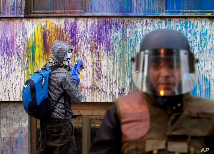 A protestor uses a water gun to spray with colored paint on the  Public Revenue Office building during an anti-government protest in downtown Skopje, Macedonia.