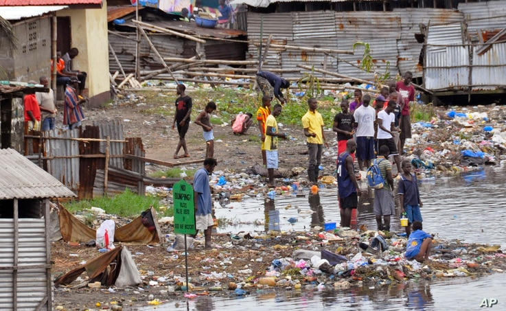 People stand on the shoreline at West Point, Monrovia, Liberia, Aug. 27, 2014.
