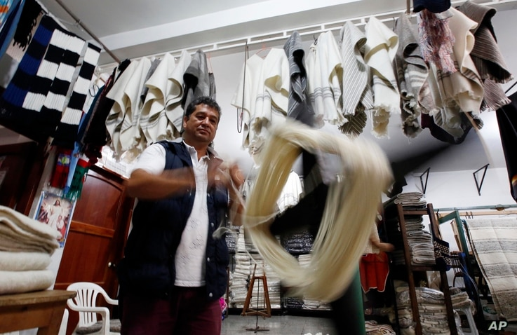 Carlos Antonio Nino spools wool to make ruanas, a traditional Colombian garment, in Nobsa, Colombia, Aug., 25, 2017. A ruana is a poncho-style outer garment typical of the Andes region of Colombia.