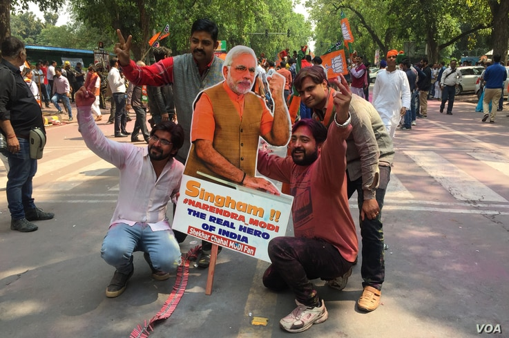 Bharatiya Janata Party workers celebrate, holding up a cardboard cut-out of Prime Minister Modi, in New Delhi, India, March 11, 2017. (A. Pasricha/VOA).
