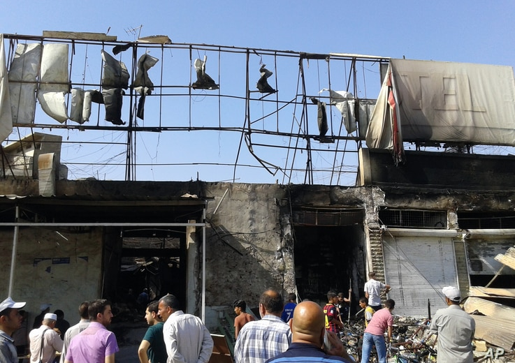 People inspect buildings damaged by an Iraqi government airstrike in the northern city of Mosul, Iraq, June 28, 2014.