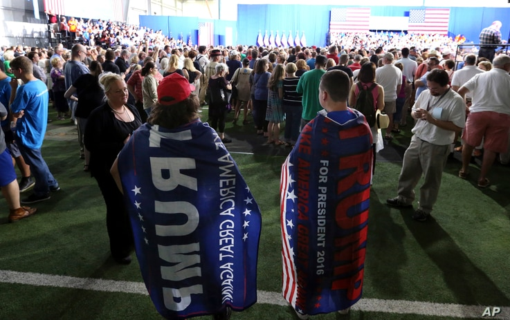 Brien Wedlock, right, and Matt Catanzaro are pretty much ignored as they wear Donald trump capes at a campaign rally for Democratic presidential candidate Hillary Clinton, in Scranton, Pa., Aug. 15, 2016.