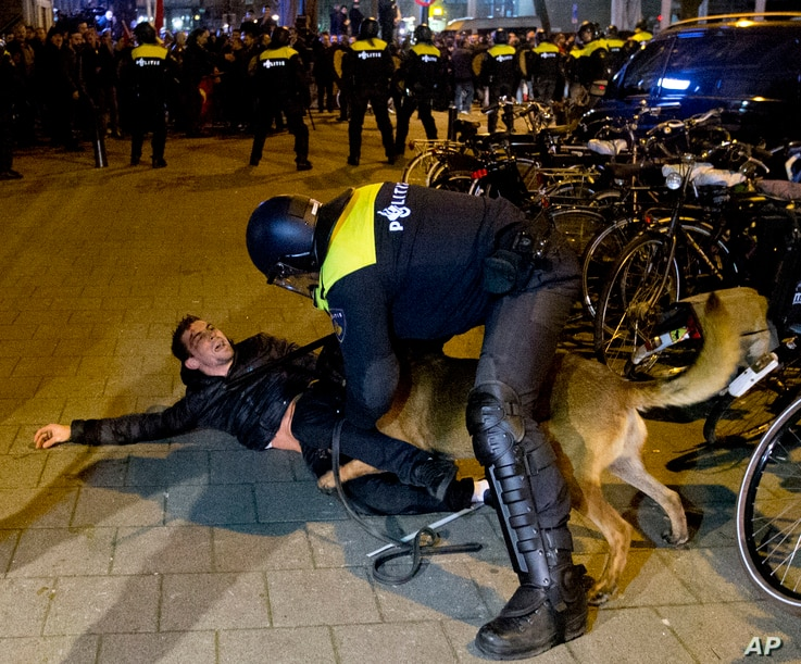 A Dutch riot policeman tries to get his dog to let go of a man after riots broke out during a pro-Erdogan demonstration at the Turkish consulate in Rotterdam, Netherlands, March 12, 2017.