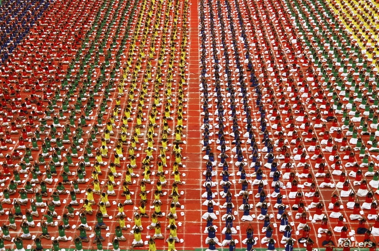 Students practice yoga in the lawns of their school ahead of International Day of Yoga, in Chennai, India, June 19, 2015.