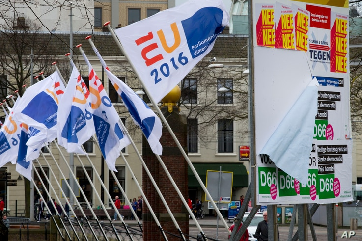 """Flags of the Dutch EU presidency and campaign posters for a recent non-binding referendum on the EU-Ukraine association agreement are seen in The Hague, Netherlands, April 6, 2016. The resulting """"no"""" was greeted with concern in the West, but with del..."""