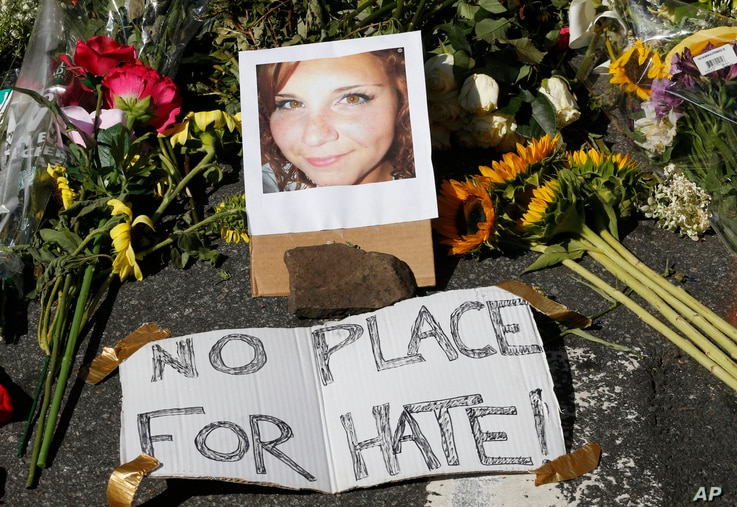 A makeshift memorial of flowers and a photo of victim, Heather Heyer, sits in Charlottesville, Va., Aug. 13, 2017.
