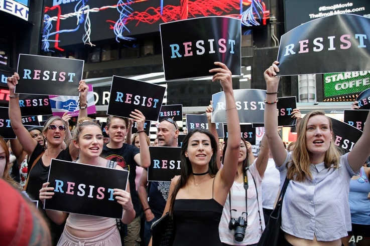 FILE - Protesters gather in Times Square, July 26, 2017, in New York, where a rally was held after President Donald Trump's announcement of a ban on transgender troops serving anywhere in the U.S. military.