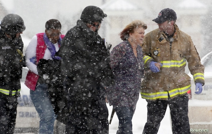 Two women are evacuated from a Colorado Springs, Colorado building where a shooter was suspected to be holed up November 27, 2015.