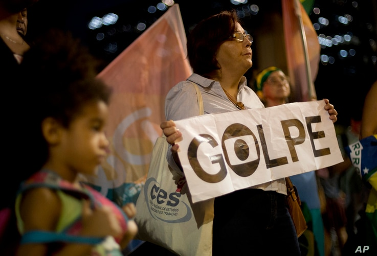 """A pro-government demonstrator holds a sign that reads in Portuguese """"Coup"""" during a protest against the impeachment of Brazil's President Dilma Rousseff in Rio de Janeiro, Brazil, May 11, 2016."""