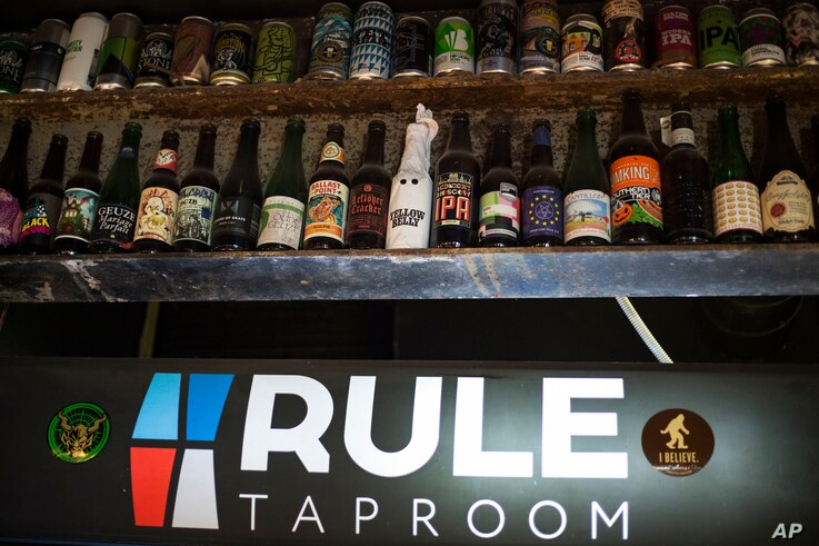 In this July 21, 2017 photo, bottles of various beer are displayed at the RULE Taproom pub in Moscow, Russia.