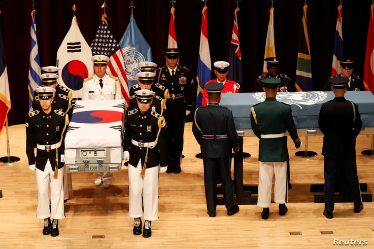 South Korean and the United Nations Command honor guards carry the remains of United Nations Command and South Korean soldiers killed in North Korea in the 1950-53 Korean War during the mutual repatriation ceremony of soldiers' remains between South ...