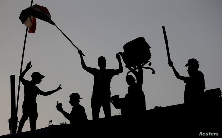 raqi protesters stand on concrete blast walls during an anti-government protest near a government building in Basra, Iraq, Sept. 7, 2018.