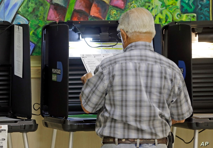 A voter reviews his ballot as he prepares to vote, Aug. 30, 2016, at Precinct 331, in Hialeah, Florida.