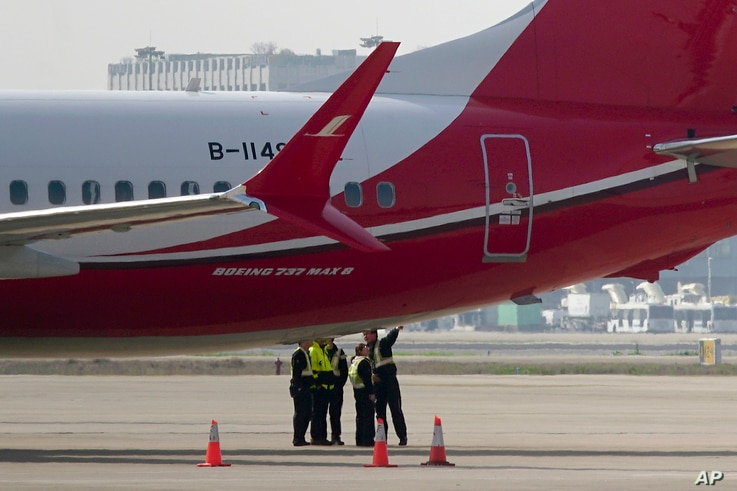 Ground crew chat near a Boeing 737 MAX 8 plane operated by Shanghai Airlines parked on tarmac at Hongqiao airport in Shanghai, China, March 12, 2019.