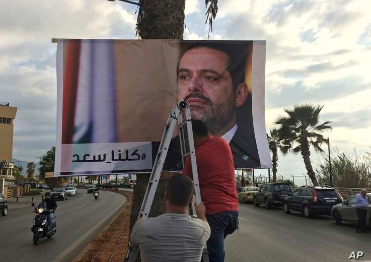 """Workers hang a poster of outgoing Prime Minister Saad al-Hariri with Arabic words that read """"We are all Saad,"""" on a seaside street in Beirut, Lebanon, Nov. 9, 2017. Hezbollah has called on Saudi Arabia to stay out of Lebanese affairs, saying the resi"""