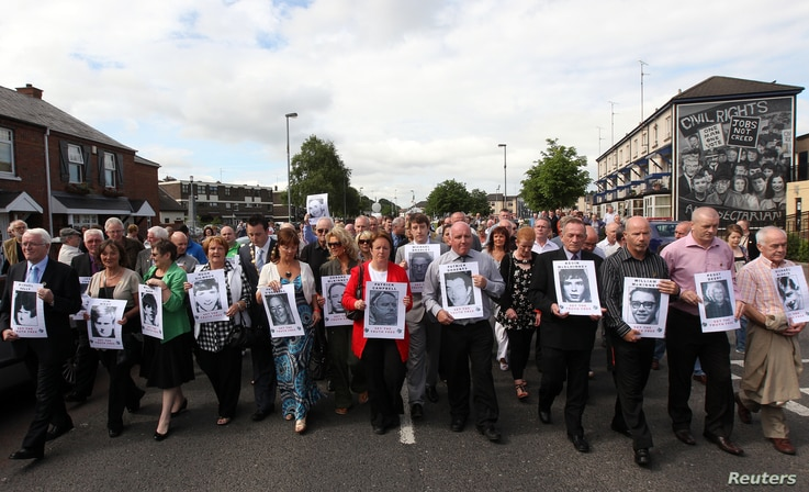 FILE - Relatives of those killed during Bloody Sunday make their way from the Bogside to the Guildhall to read the Saville report, Londonderry in Northern Ireland, June 15, 2010.