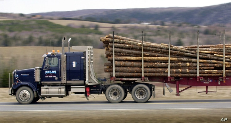 FILE - A load of Maine logs is trucked through Fort Fairfield, Maine, by a Canadian driver on his way to a mill in New Brunswick, Canada, April 21, 2004.