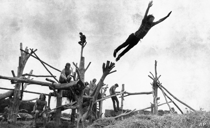 FILE - Rock music fans sit on a tree sculpture as one leaps onto a pile of hay during the Woodstock Music and Art Festival held on a cow pasture at White Lake in Bethel, New York, Aug. 15, 1969.