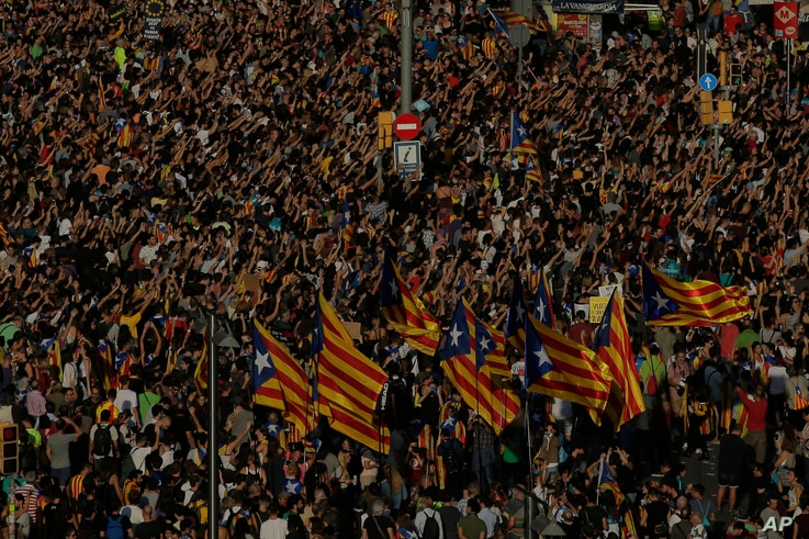 Protesters with ''esteladas'' or Catalonia independence flags pack the University square during a one-day strike in Barcelona, Spain, Tuesday Oct. 3, 2017. Labor unions and grassroots pro-independence groups are urging workers to hold partial or full