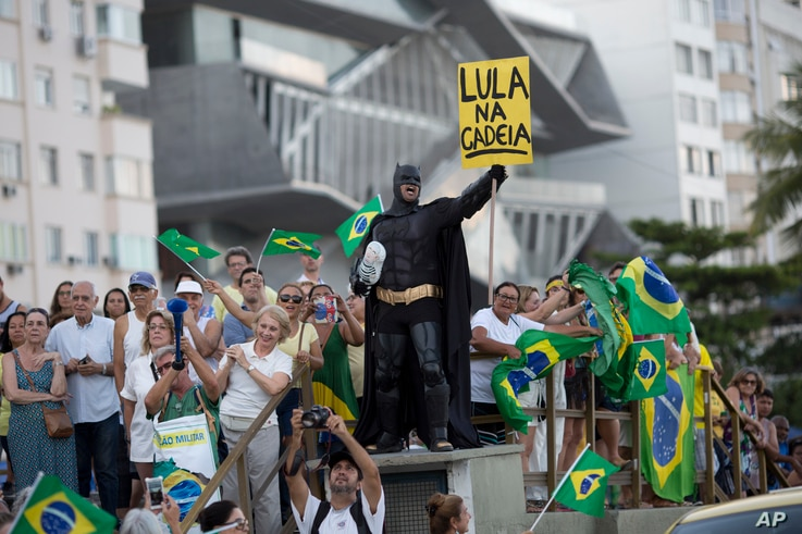 """A demonstrator dressed as Batman holds a sign that reads in Portuguese """"Lula in Prison"""" during a protest against former President Luiz Inacio Lula da Silva on Copacabana beach, in Rio de Janeiro, Brazil, Jan. 23, 2018."""