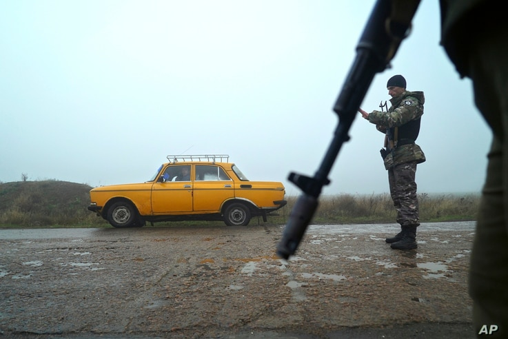 A car is stopped at a checkpoint manned by Ukrainian police officers, in Berdyansk, south coast of Azov sea, eastern Ukraine, Nov. 27, 2018.