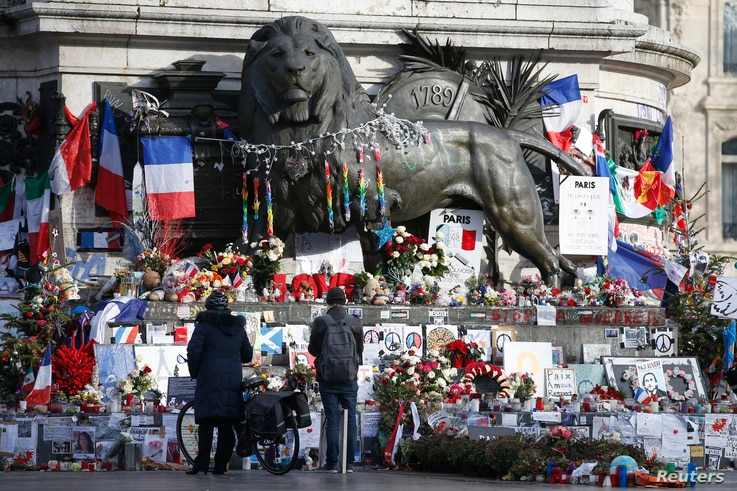 People look at flowers and other tributes to victims of last year's January and November shooting attacks near the statue at the Place de la Republique in Paris, France, January 6, 2016.