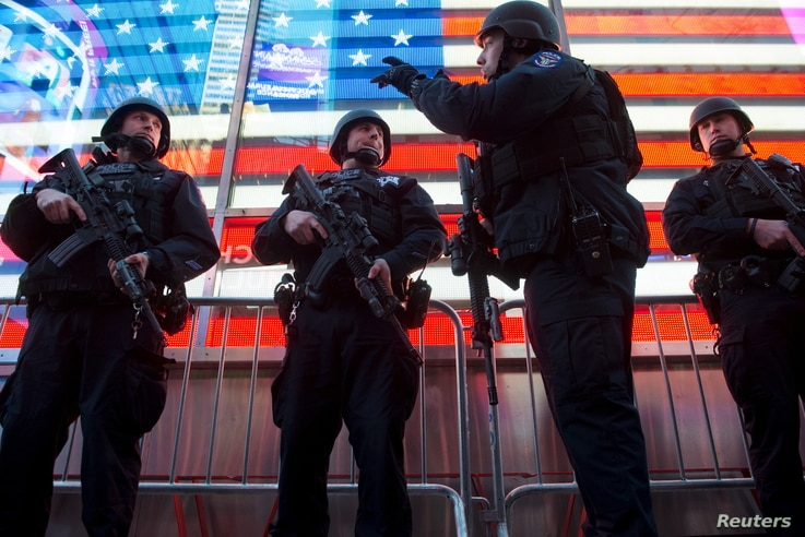 Armed New York City police officers with the special operation division Strategic Response Group stand guard in Times Square in New York, as security was tightened following the deadly attacks in Paris, Nov. 14, 2015.