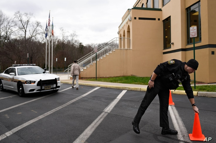 A Loudoun County (Va.) sheriff's deputy moves a traffic cone at the All Dulles Area Muslim Society Center in Sterling, Va., where security guards resigned because they felt they could no longer protect the mosque amid anti-Muslim sentiment, Dec. 18, ...