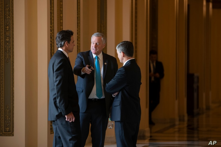 Rep. Mark Meadows, R-N.C., center, chairman of the conservative House Freedom Caucus, flanked by Rep. Tom Graves, R-Ga., Rep. Jeb Hensarling, R-Texas, talk before a series of votes in the House, at the Capitol in Washington, Thursday, June 21, 2018. ...