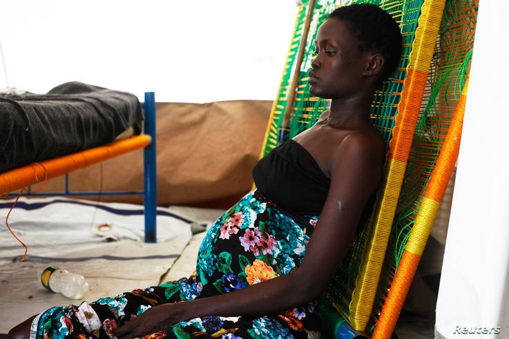 A pregnant woman sits on the floor at a hospital in Minakaman, Lakes State, South Sudan, June 26, 2014.
