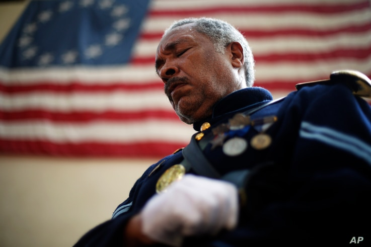 Civil War re-enactor Cpl. Robert Fuller Houston with the 3rd Regiment Infantry, lowers his head during a prayer at a ceremony Wednesday, Sept. 11, 2013, marking the 12th anniversary of the 9/11 terrorist attacks at the Betsy Ross House in Philadelphi