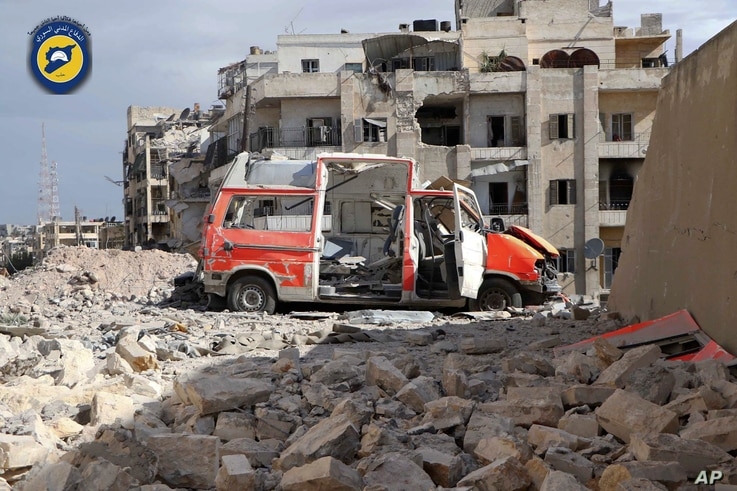 """In this photo provided by the Syrian Civil Defense group known as the """"White Helmets,"""" a destroyed ambulance is seen outside the Syrian Civil Defense main center after airstrikes in Ansari neighborhood in the rebel-held part of eastern Aleppo, Syria,"""