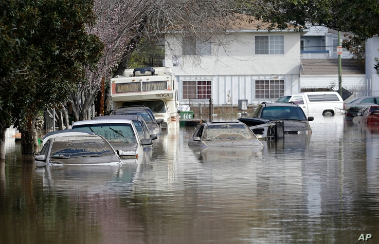 Submerged automobiles are shown on flooded Nordale Avenue in San Jose, California, Feb. 22, 2017.