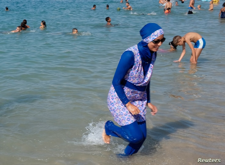 A woman wearing a burkini walks in the water August 27, 2016 on a beach in Marseille, France, the day after the country's highest administrative court suspended a ban on full-body burkini swimsuits that has outraged Muslims and opened divisions withi...