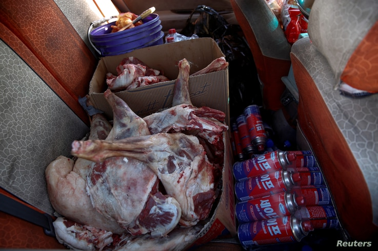 Sheep meat and cooking gas are seen in the back of a van on the road to the Mongolia-China border at Khanbogd Soum in the Gobi desert, Mongolia, Oct. 31, 2017. Smaller vehicles travel up and down the highway to the Mongolia-China border selling water...