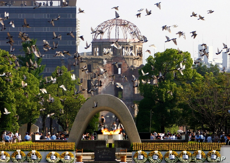 Doves fly by the Atomic Bomb Dome during the ceremony to mark the 61st anniversary of the world's first atomic bombing at Hiroshima Peace Memorial Park in Hiroshima, western Japan, Sunday, Aug, 6, 2006 (AP)