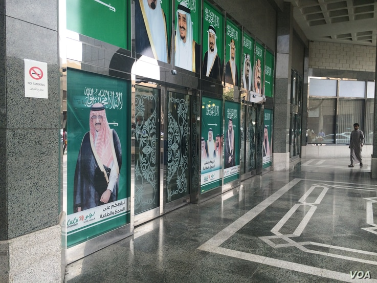 Posters on this wall outside a Riyadh mall depict the Saudi royal family, which is putting measures into place to encourage Saudi employment, Jan. 25, 2016.