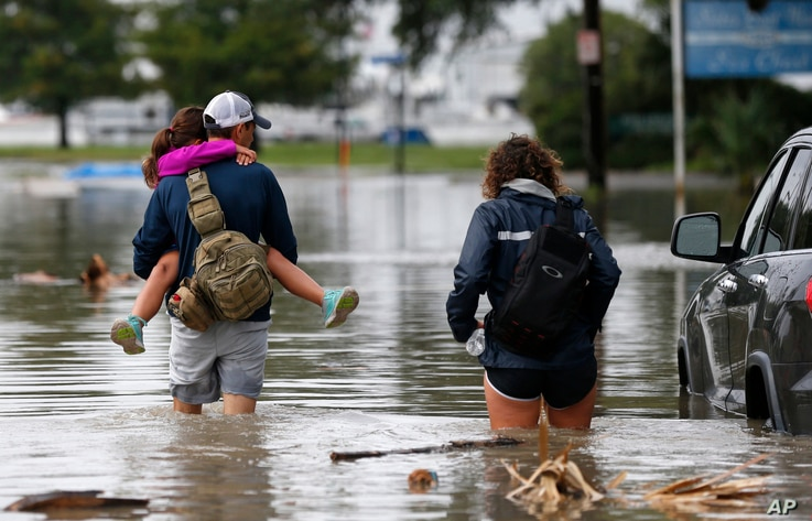 Don Noel carries his daughter Alexis, 8, with his wife Lauren, (right) as they walk through a flooded roadway in the West End section of New Orleans, June 21, 2017.