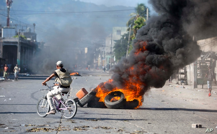 A man rides a bicycle past burning tires set by protesters demanding to know how Petro Caribe funds have been used by the current and past administrations, in Port-au-Prince, Haiti, Oct. 17, 2018.