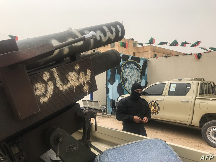 A local militiaman, belonging to a group opposed to Libyan strongman Khalifa Haftar, stands next to vehicles the group said they seized from Haftar's forces in the coastal town of Zawiya, west of Tripoli, April 5, 2019.