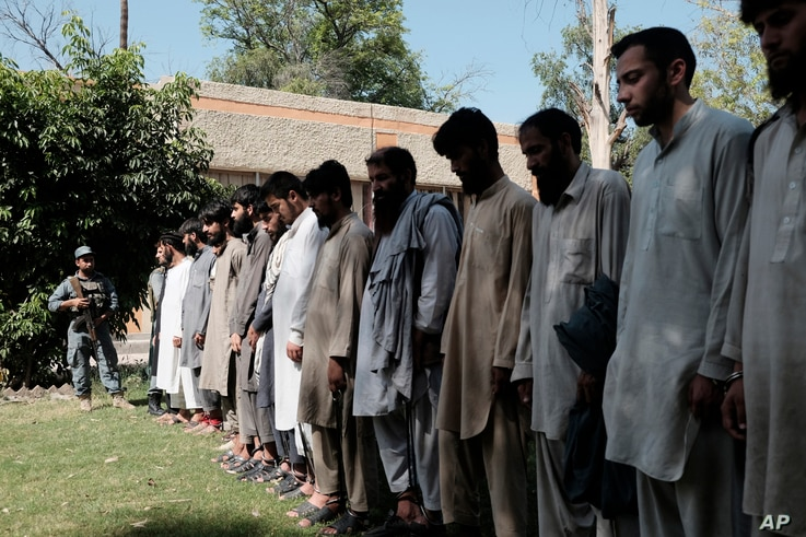 Islamic State fighters arrested by Afghan security personal stand outside the Afghan police headquarters in Jalalabad, east of Kabul, Afghanistan, May 9, 2016.