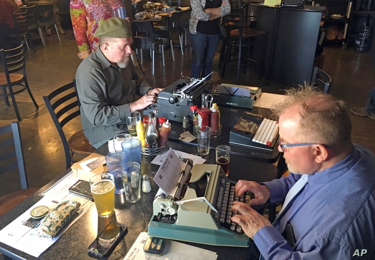 "Joe Van Cleave, left, and Rich Boucher try out various vintage typewriters at a ""type-in"" in Albuquerque, N.M., April 23, 2017."