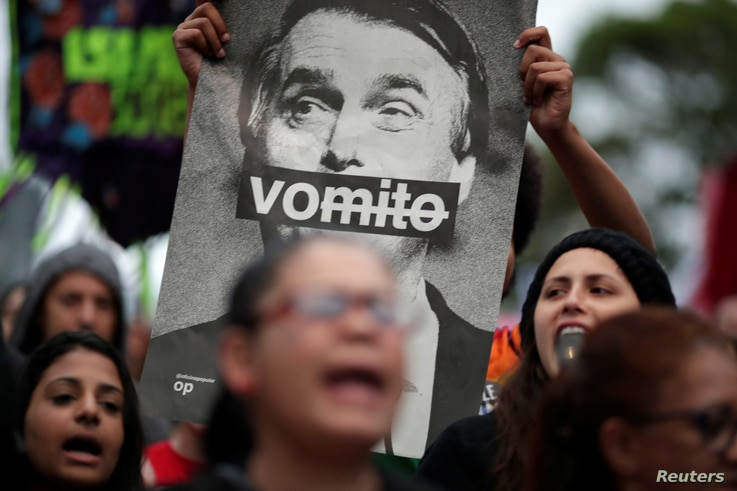 """A demonstrator shows a picture of Brazilian presidential candidate Jair Bolsonaro, that reads: """"Vomit"""" during a protest against him at Paulista Avenue in Sao Paulo, Oct. 6, 2018."""