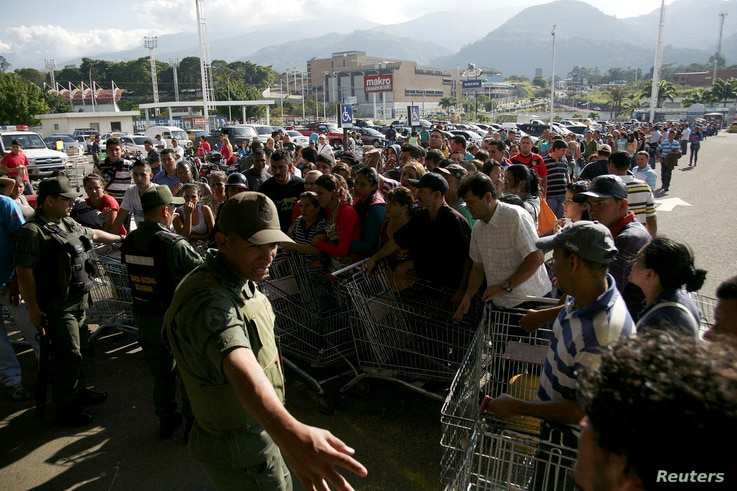 National guards control the entrance of a private supermarket as people line up to enter in San Cristobal, Venezuela, Jan. 15, 2015.